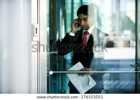 A man on his phone near a glass door. - stock photo