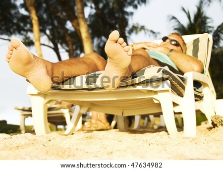 a Man on holiday on a tropical island resting in the late afternoon sun - stock photo