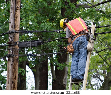 A man on ladder working on the power lines.