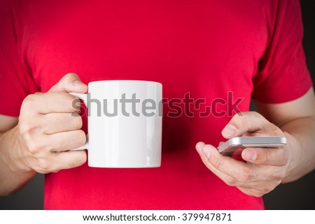 A man on Red T-shirt Holding Smart phone and Coffee mug on Black background - stock photo