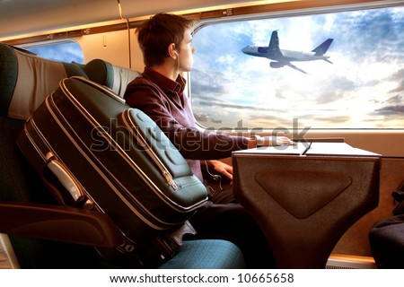 a man on the train looking a sunset and a airplane
