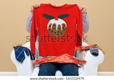 A man opening Christmas presents to discover he got a Christmas themed jumper to go along with the usual socks and tie. - stock photo