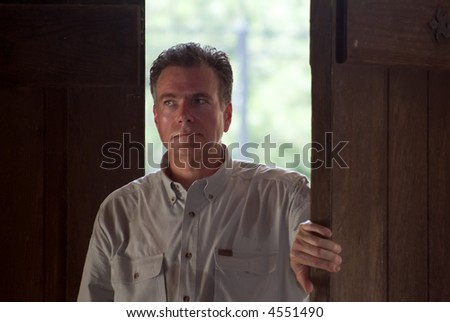 A man opening large wooden doors with a look of anticipation on his face. - stock photo