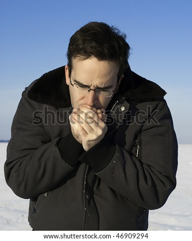 A man outside in the winter is warming his hands by breathing on them.