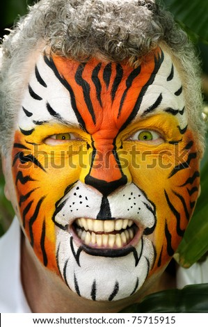 A man painted like a tiger making an angry expression. - stock photo