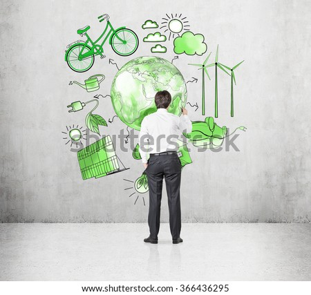 A man painting symbols of alternative energy sources in green colours on a concrete wall. Green Earth in the middle. Concept of clean environment. - stock photo