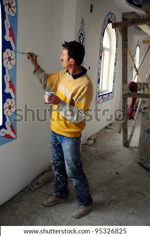 a man painting wall