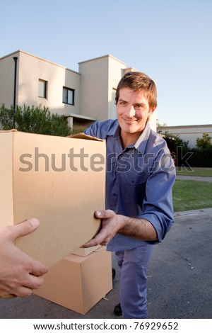 A man passing a moving box to another person