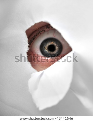 A man peaking through a peice of paper to be a spy. - stock photo