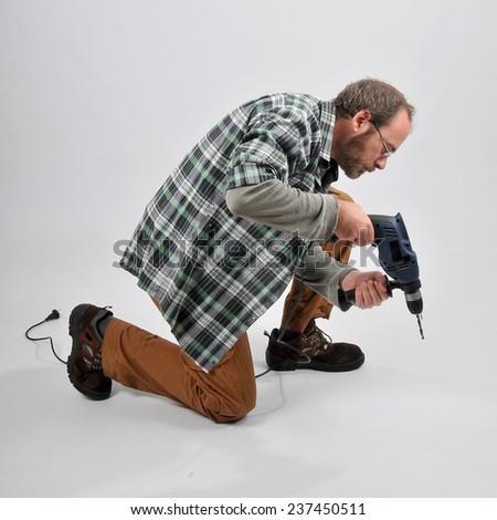 A man pierces with a drill - stock photo