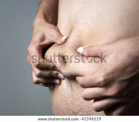 A man pinches his body fat.
