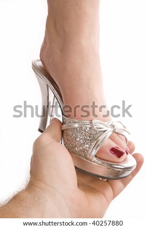 A man placing a shiny silver shoe on a woman's foot just like Cinderella.