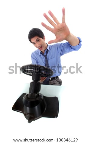A man playing a car game in his office. - stock photo