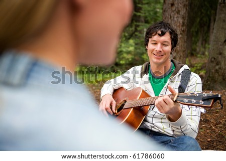 A man playing a guitar and singing for a woman - stock photo