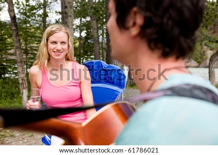 A man playing a guitar outdoors for a girl - stock photo
