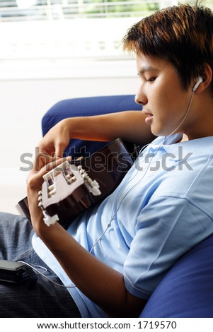 A man playing a guitar while listening to music - stock photo