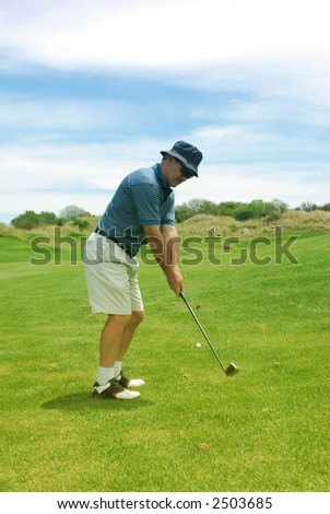 A man playing golf on the fairway. Golf club is in motion. - stock photo