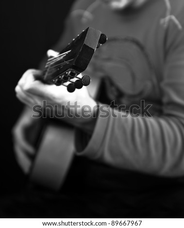 a man playing on a guitar - stock photo
