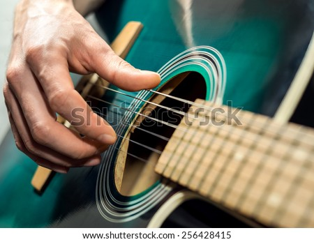 A Man playing on the acoustic guitar - stock photo