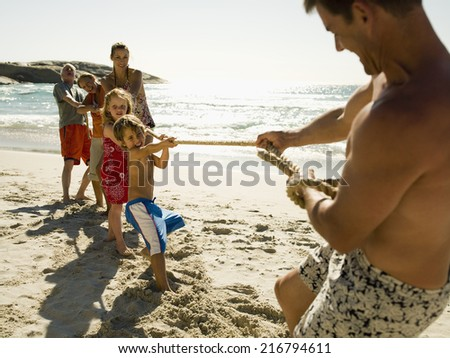 A man playing tug of war against his Family. - stock photo