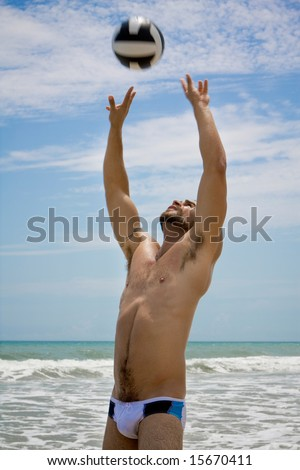 A man playing volleyball at the beach