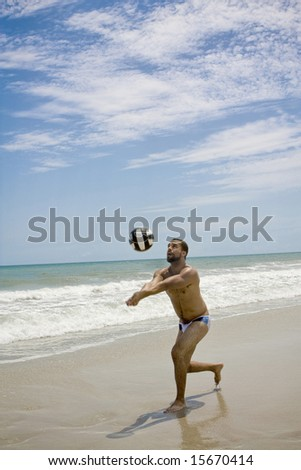 A man playing volleyball at the beach - stock photo