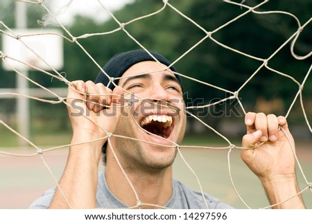 A man playing with a soccer goal net, screaming and laughing through it, while holding onto it. - horizontally framed - stock photo