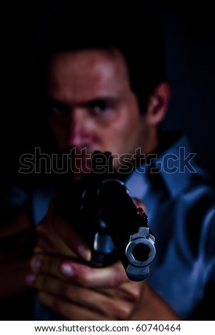 A man pointing a gun with an angry look on his face. - stock photo