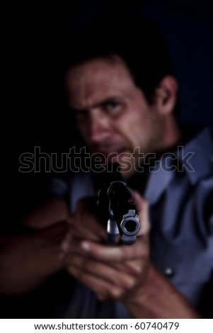 A man pointing a gun with an angry look on his face.