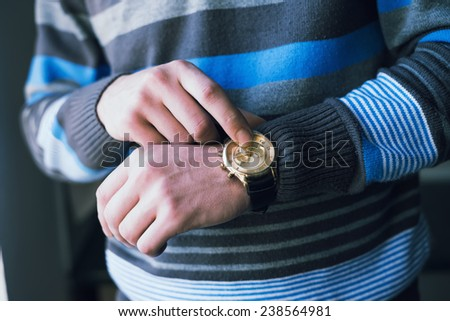A man pointing at his watch - stock photo