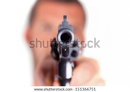 A man pointing his gun revolver. Selectively concentrated on the front of the gun. - stock photo
