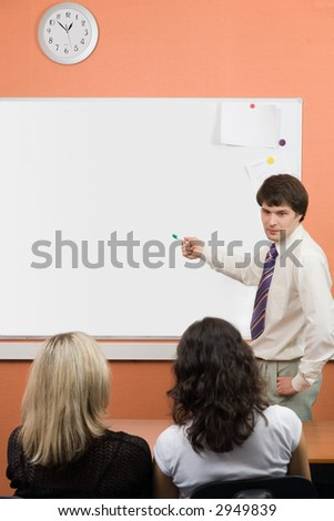 A man pointing on blackboard on seminar\meeting - stock photo