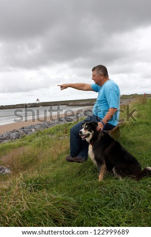 A man pointing out to sea with his dog by his side