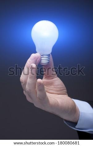 a man pointing to the illuminated bulb - stock photo