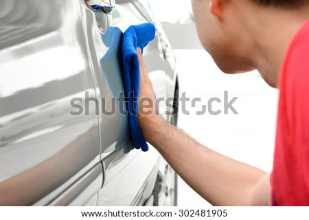 A man polishing car with microfiber cloth, car detailing (or valeting) concept - stock photo