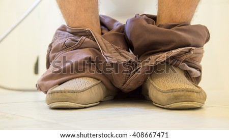 A man pooping in a toilet - stock photo