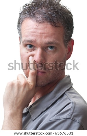 A man posing with his finger beside his nose, looking at the camera, isolated on white.