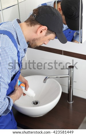 A Man pouring a Pipe cleaner in drain pipe  - stock photo