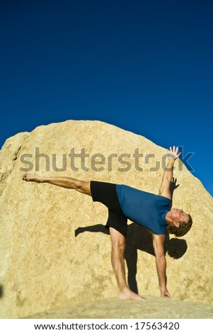 A man practices yoga on the boulders in Joshua Tree National Park, California, on a summer evening.