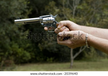 A man prepares to shoot his .22 pistol.