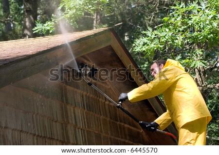 a man pressure washing a garage - stock photo