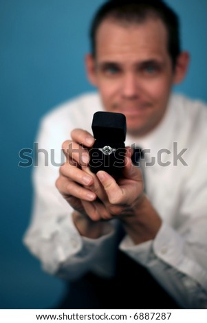 A man proposing and holding up an engagement ring - stock photo