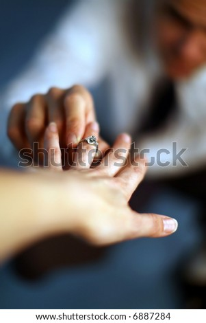 A man proposing and putting a ring on a woman's finger - stock photo