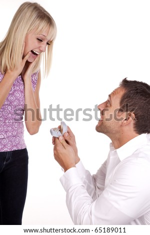 A man proposing marriage to his woman with a diamond ring.  The woman showing her excitment with the expression on her face. - stock photo