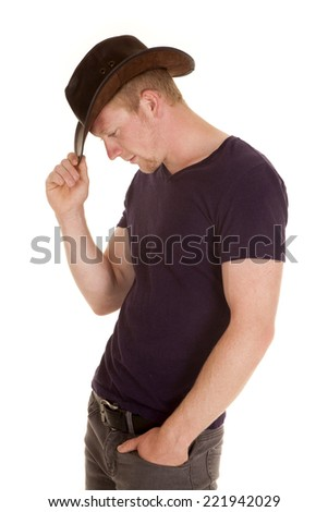 A man pulling down his western hat looking down. - stock photo