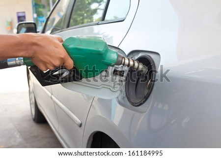 A man pumping gas in to the tank  - stock photo