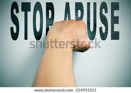 a man punching the text stop abuse, depicting the concept of the fight against all kind of abuse, such as domestic abuse or child abuse - stock photo