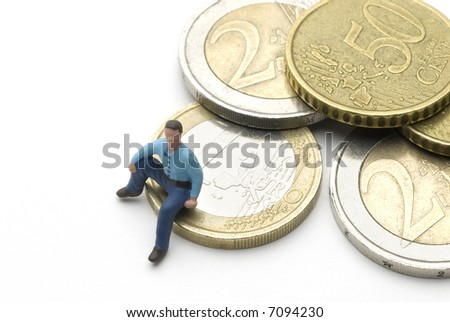 a man (puppet) sitting on some Euro coins - stock photo