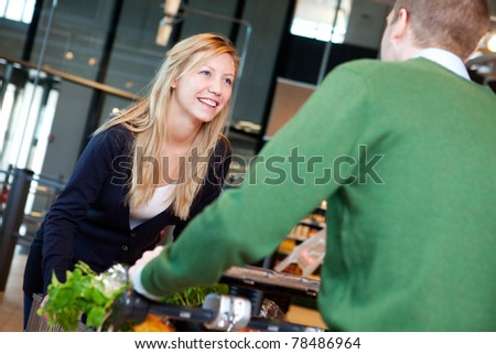 A man pushing a woman standing on a grocery cart - stock photo