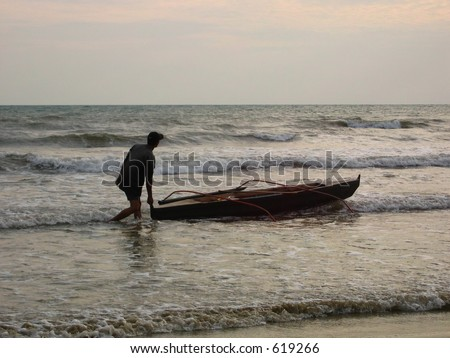 A man pushing his boat out to sea at sunset - stock photo